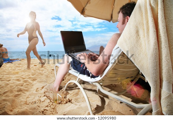 Man working on laptop at tropical beach in Hawaii
