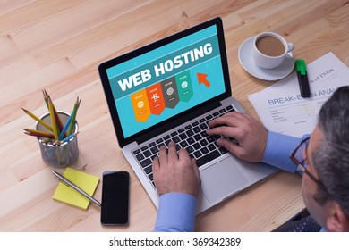 Man working on laptop with WEB HOSTING on a screen