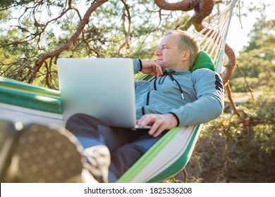 A man working on a laptop while lying in a hammock in the woods. Self-isolation, freelancing, remote work and distancing. Top view of Scandinavian landscape
