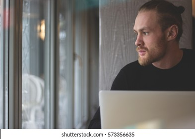 Man is working on laptop while sitting at cafe