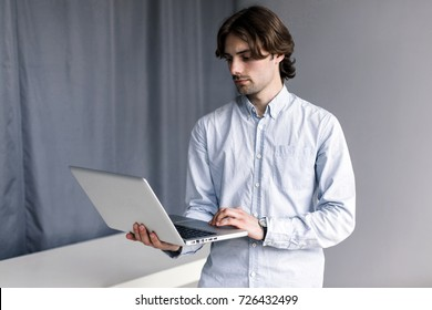 A man working on a laptop.  A young freelancer.