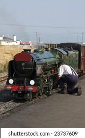 A man working on a miniature steam train