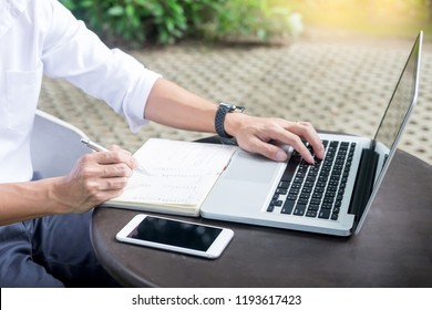 Man working on modern laptop sitting outside natural hardwood desk with green flora background sunlight day outdoor, everywhere you are from laptop concept