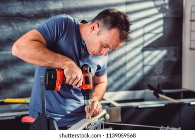 Man working on a new kitchen installation and using a cordless drill