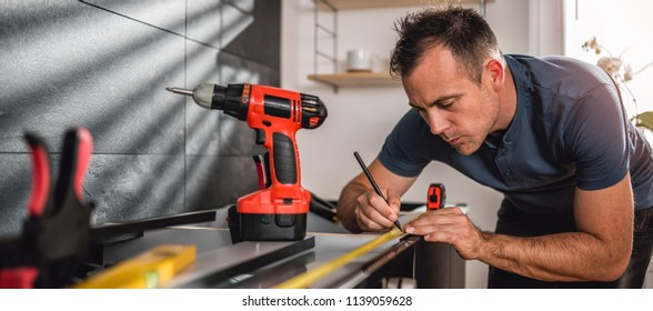 Man working on a new kitchen installation and using a measuring tape