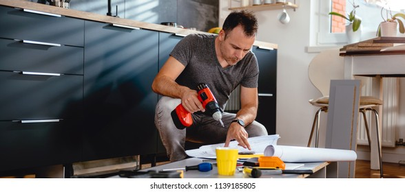 Man working on a new kitchen installation and looking at blueprints
