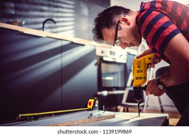 Man working on a new kitchen installation and using electric drill