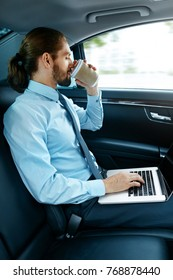 Man Working On Notebook And Drinking Coffee in Car. Attractive Successful Businessman in Formal Wear Going To Work With Laptop And Hot Drink In Car. Business Travel. High Resolution.