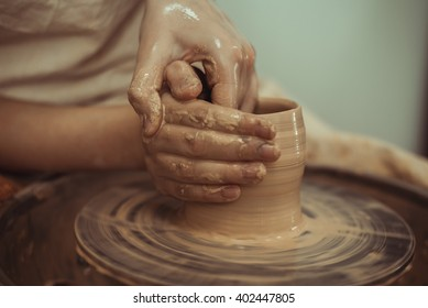 man working on the potter's wheel, making the dishes with their own hands