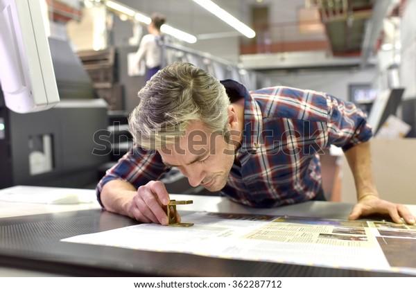 Hombre trabajando en una máquina de impresión en fábrica