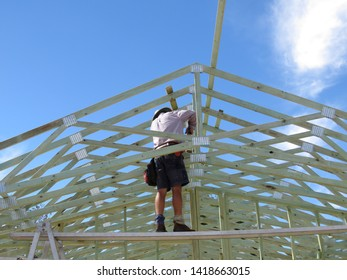 Man working on the roof of a timber frame house