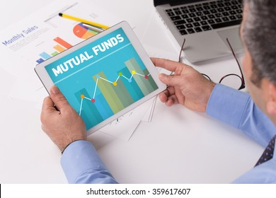 Man working on tablet with MUTUAL FUNDS on a screen