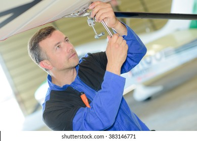 Man working on the underside of an aircraft