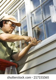 Man working on a window to remove old glazing with a chisel.