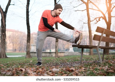 Man working out in the city park and stretching muscles
