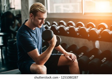 man working out in gym doing exercises with dumbbells. Pretty young man training in the gym