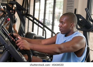 Man working out on a stationary cycle machine in a fitness club.