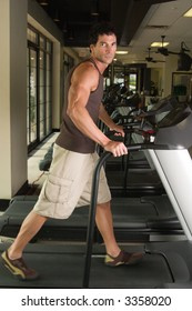 Man working out on a treadmill in a fitness center.  There is motion blur on the feet.