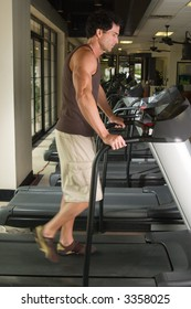 Man working out on a treadmill in a fitness center.  His feet are blurred from the walking motion.