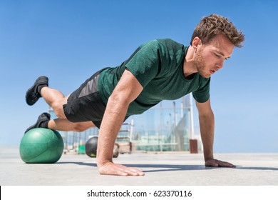 Man working out strength training doing incline push-ups workout at outdoor gym balancing on stability medicine ball with one leg raised. Bodyweight pushups exercises. Push-up variation.