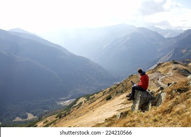 man working outdoors with laptop in High Tatras Mountains in Cloudy Day. Slovakia, Poland
