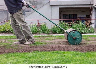 Man in working outfit pulls lawn roller behind. Necessity after long winter and spring for flat surface. Landscaping on the garden. Summer worker