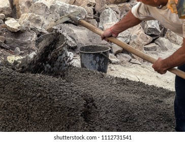 Man working outside with a shovel. Construction, cement, rocks and concrete