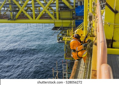 Man working overboard. Abseiler climbing and hanging at the edge of oil and gas platform in the middle of sea.