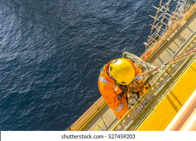 Man working overboard. Abseiler complete with personal protective equipment (PPE) climbing the edge of oil and gas rig platform in the middle of sea.