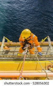 Man working overboard. Abseiler complete with personal protective equipment (PPE) climbing and hanging at the edge of oil and gas rig platform in the middle of sea.
