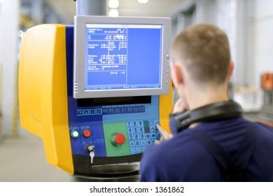 Man working at programmable machine. Sheet metal bending. Focus on monitor