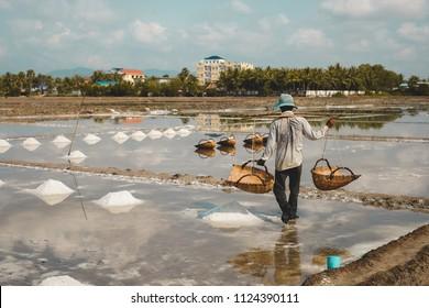 Man working in salt fields in Kampot, Cambodia