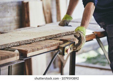 Man working in sawmill. Hands of the worker with protective glove.