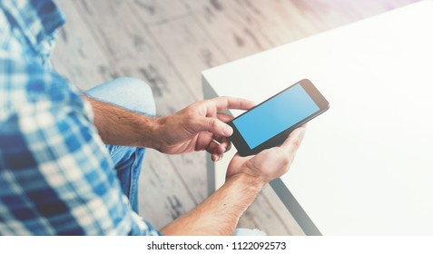 Man Working With Smartphone, sitting at a cafe. Clipping path included.