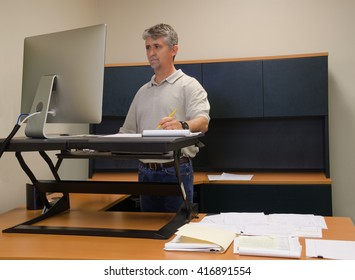 A man is working at a stand up desk in an office where he works because standing is healthier than sitting all day. Live healthy, do not sit all day.