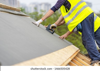 Man working with stapler and special waterproof bitumen membrane. Mature and professional contractor in protective uniform wear standing on roof top of new modern building construction
