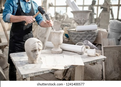 Man working with stone vase at the working place in the old studio. Close-up view with no face