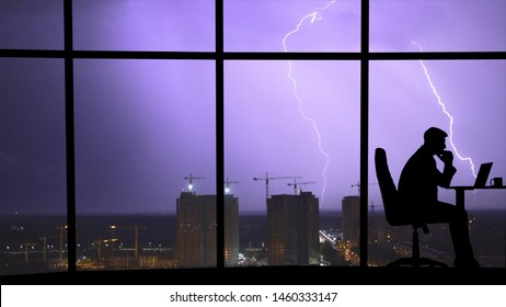 The man working at the table near a window on a city lightning background
