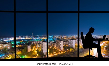 The man working at the table near a window with a night city view
