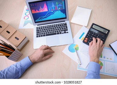 Man working at table in office, top view. Financial trading concept