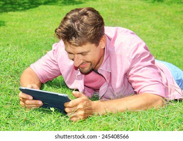 man working with tablet computer outdoor in park
