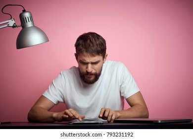 man working with a tablet on a pink background