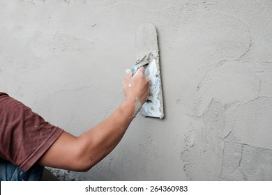 Man working trowel on wet cement wall