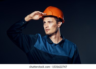 A man in a working uniform is an orange helmet Construction engineer providing services