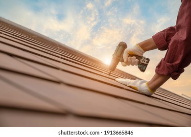 Man working wear gloves, using pneumatic nail gun repairing concrete or CPAC cement roofing tiles on top of roof under construction residential building.DIY handmade with free space and background.