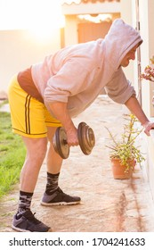 Man workout in house yard using weights