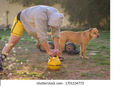 Man workout outdoors in house yard with his dog