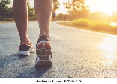 Man workout wellness concept : Close up runner feet with sneaker shoe running on road in the park. Focus on shoe. Shot in morning time, sunlight and warm effect with copy space for text or design