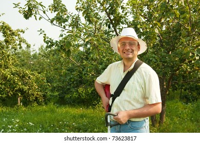 A man works with cordless grass trimmer in garden