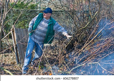A man works in the garden, fires a bonfire, removes, cleans the territory, cuts dry branches near blue river